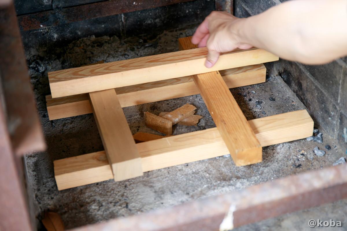 火起こしの写真 井形に組んで、中央に着火剤や燃えやすい木を置く 飯盒炊飯 炉の使い方