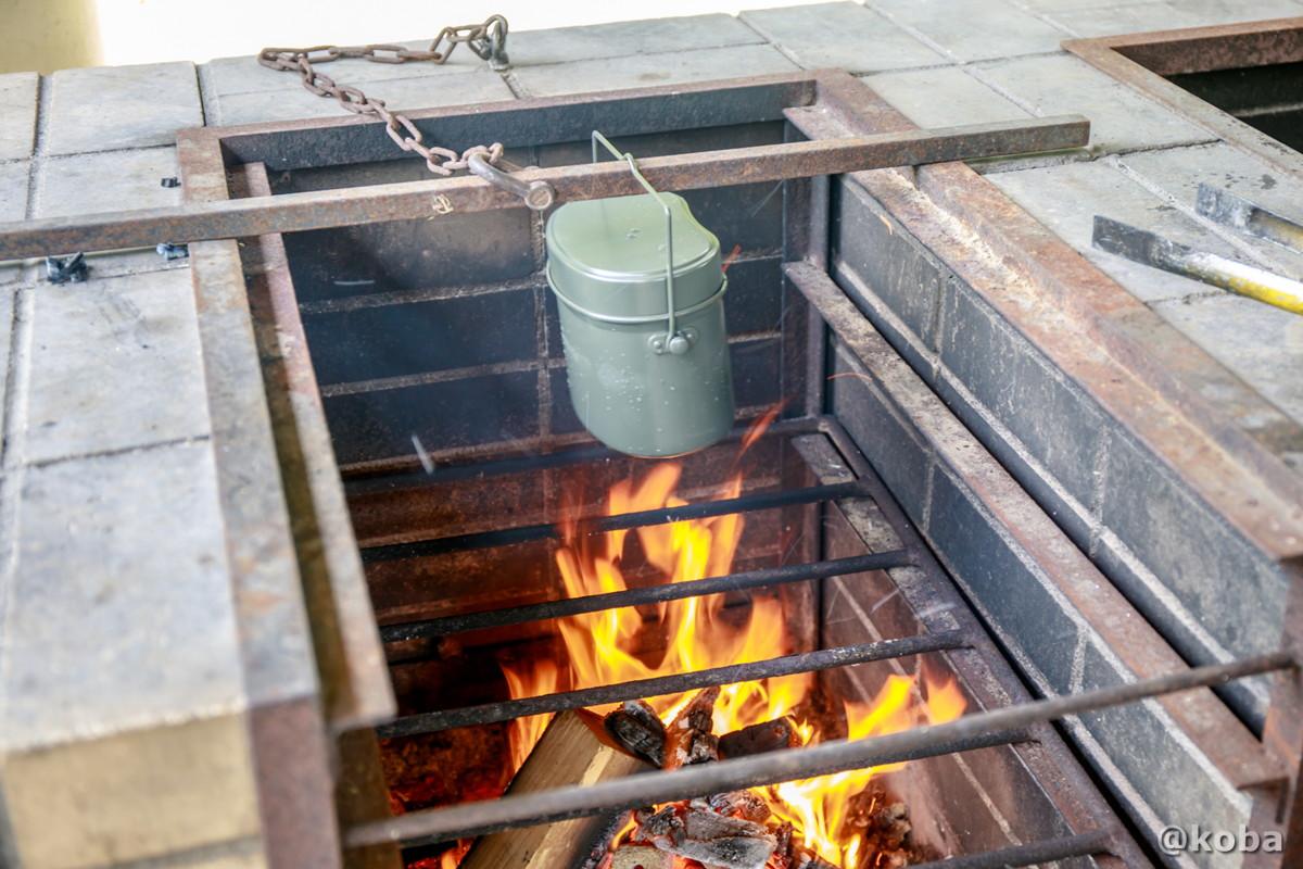 飯盒を鉄のバーに引っ掛ける最初は弱火 飯盒炊飯 炉の使い方