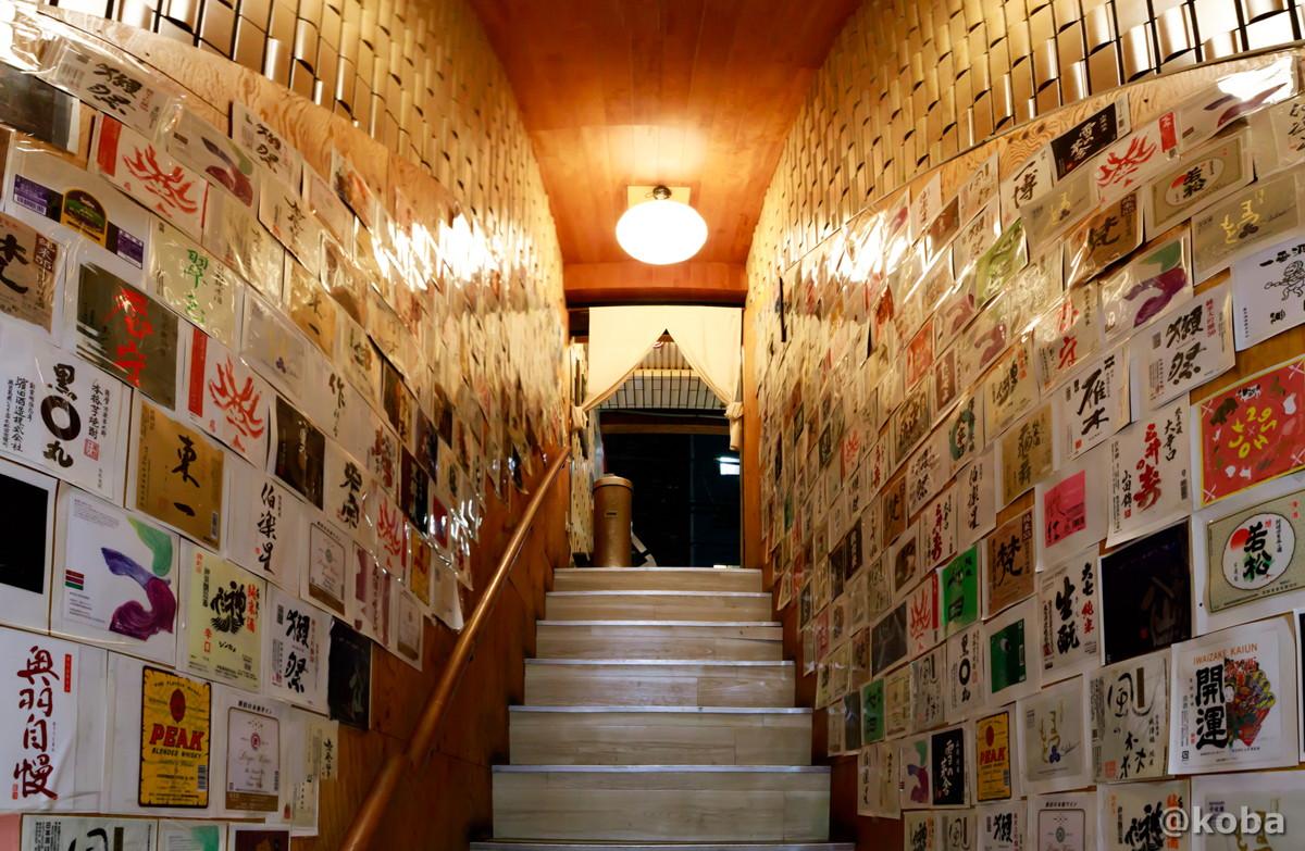 壁一面お酒のラベルが貼られた階段 錦糸町 しゅはり