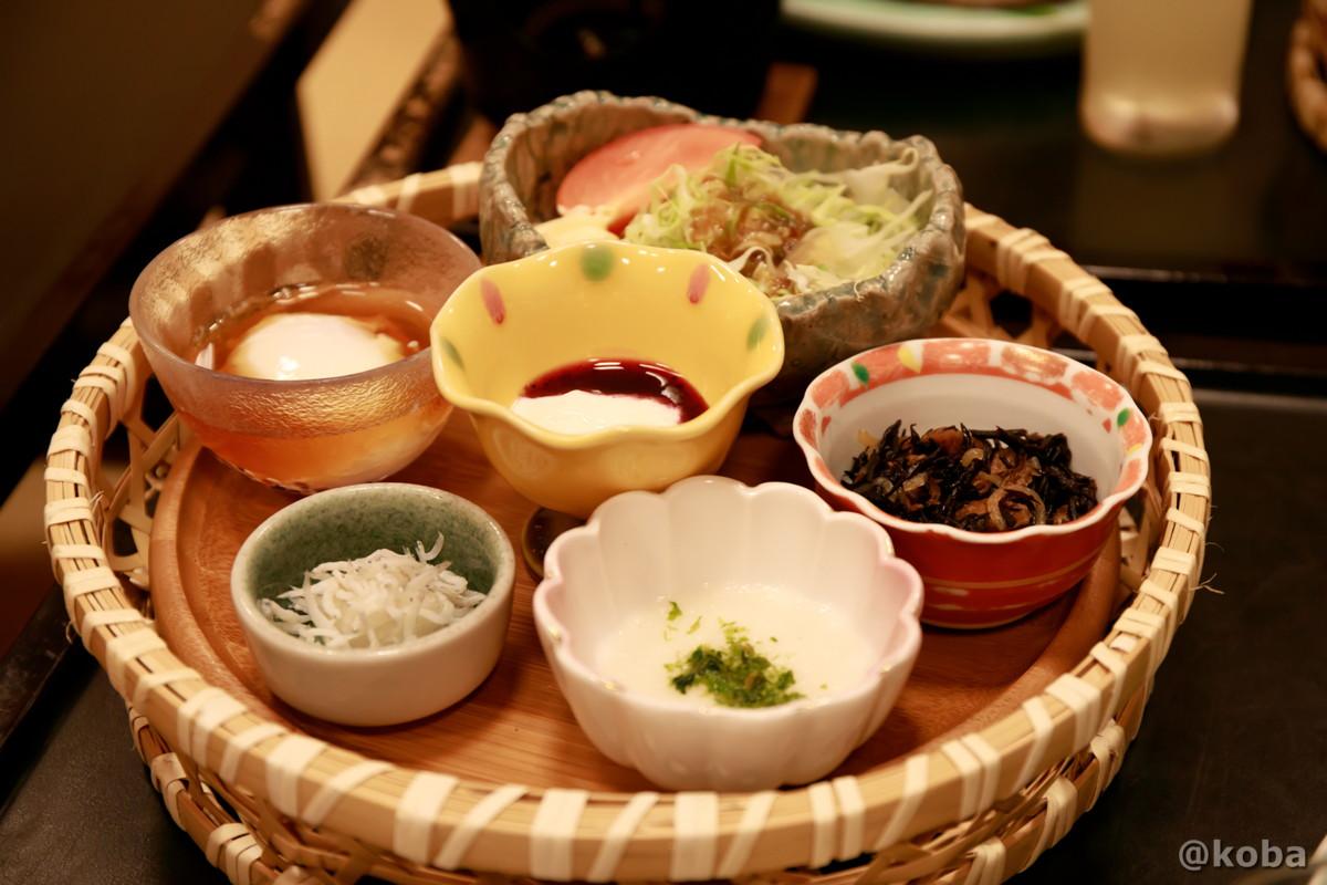 朝食、丸い籠に載った料理の写真(シラス とろろ 温玉 煮物 サラダ ヨーグルト)たんげ温泉 美郷館