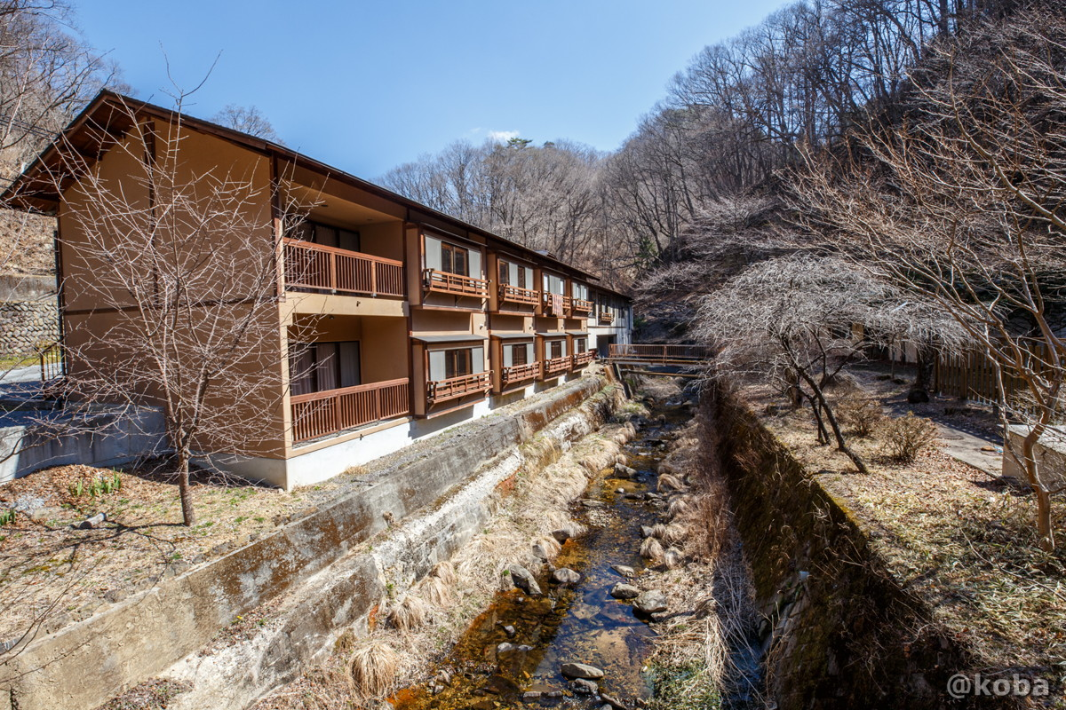 内山峠 初谷温泉 小川沿いに建つ一軒宿木造建築外観の写真|長野県佐久市